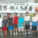 帰島した狩俣小のメンバーと個人戦優勝の根間君(左から9人目)=9日、宮古空港