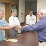 国保運営協の松川会長(左)から下地市長に国保税率を引き下げる条例の一部改正案が答申された=11日、市長室