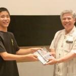 「島の時間」DVD完成披露の前にDVDを川上教育長に贈呈する仲村君(左)=16日、シネマパニック宮古島