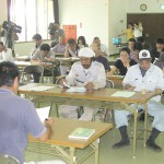 産地を認定するシールの説明に耳を傾ける生産者=18日、上野農村環境改善センター