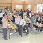 新しい地域拠点の完成を祝い祝杯を上げる地域住民ら関係者=22日、七原コミュニティセンター