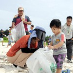 400人が参加し、空き缶やペットボトルなどのごみを拾い集めた=22日、トゥリバー海岸