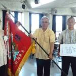 総合優勝した大木区の役員に賞状と優勝旗が下地村長(左)から授与された=25日、多良間村中央公民館